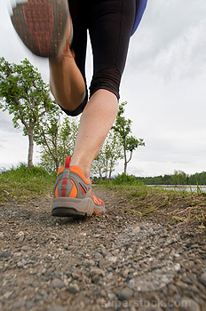 Closeup of a trail runners feet running on a gravel trail